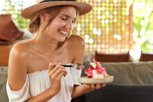 Beautiful young cheerful woman with bare shoulders, eats delicious piece of cake, comes on friend`s birthday party at cafe, dressed in summer clothing, has delighted look. relaxed female with dessert
