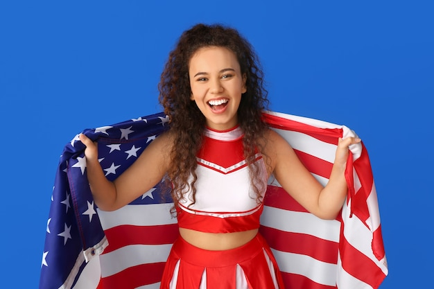 Beautiful young cheerleader with usa flag on color surface