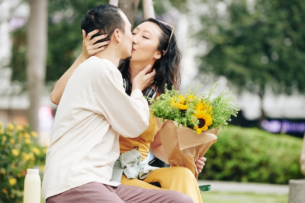 Beautiful young chinese couple in love kissing on bench in park when having romantic date