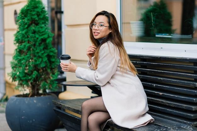 Красивый молодой китайский студент держит чашку кофе на улице