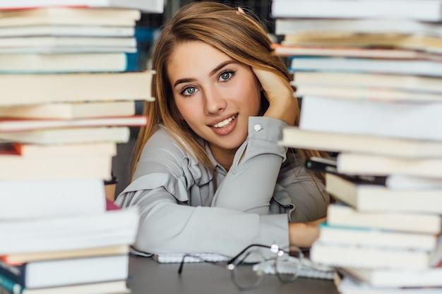 Красивая молодая женщина студент колледжа в библиотеке, позирует с очками и книгами