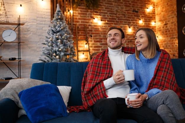 クリスマスの朝にコーヒーを飲む家で美しい若いカップル