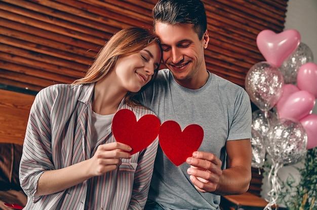 집에서 아름 다운 젊은 부부. 그들의 손에 마음을 잡고, 포옹, 키스하고 함께 시간을 보내는 사랑하는 부부