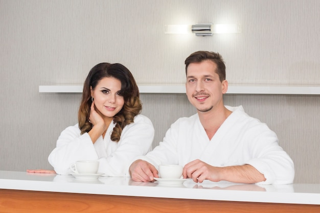 Beautiful young couple in bathrobes enjoying wellness weekend morning at hotel