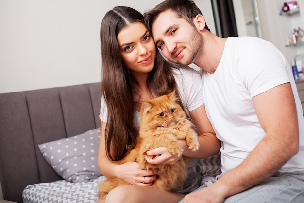 Beautiful young couple on the bed playing with a red cat