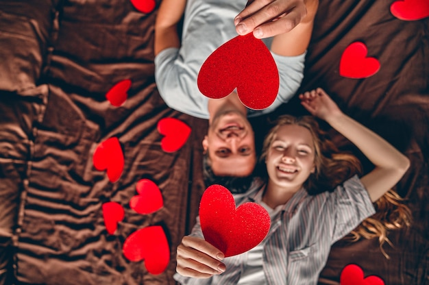 Beautiful young couple in bedroom is lying on bed with red hearts nearby celebrating saint valentines day.