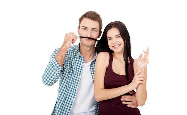 서로 결합하고 그녀의 머리에서 가짜 콧수염을 만드는 동안 웃는 아름다운 젊은 부부