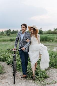 자전거와 함께 필드에 걷는 아름 다운 젊은 부부 신부와 신랑
