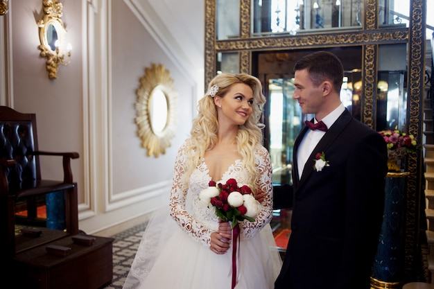 Beautiful young couple, the bride and groom. luxurious interior. looking at each other