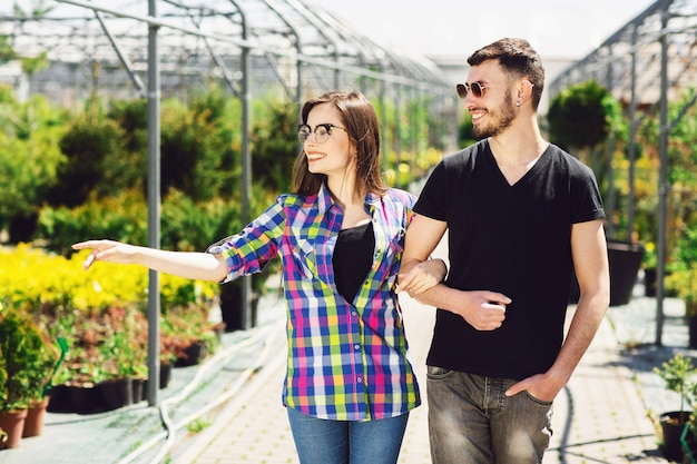 Beautiful young couple in casual clothes is choosing plants and smiling