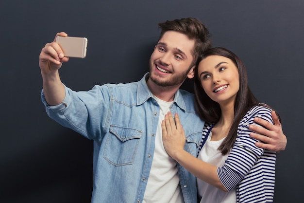 Beautiful young couple in casual clothes is making a selfie.