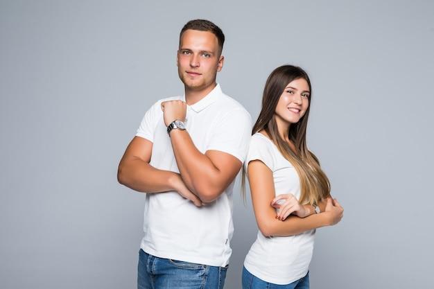 Bella giovane coppia in abbigliamento casual isolato su sfondo grigio chiaro vestita in magliette bianche