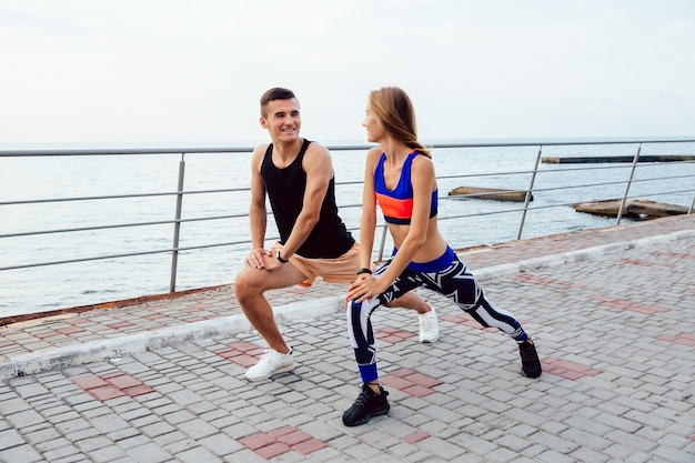 Beautiful young couple doing sports exercises, looking at each other, stretching the body
