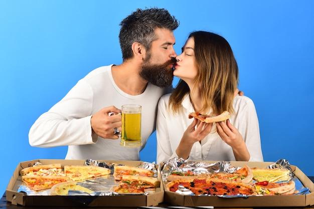 ピザを食べてビールを飲み、愛の食べ物と飲み物にキスをする美しい若いカップル幸せな家族