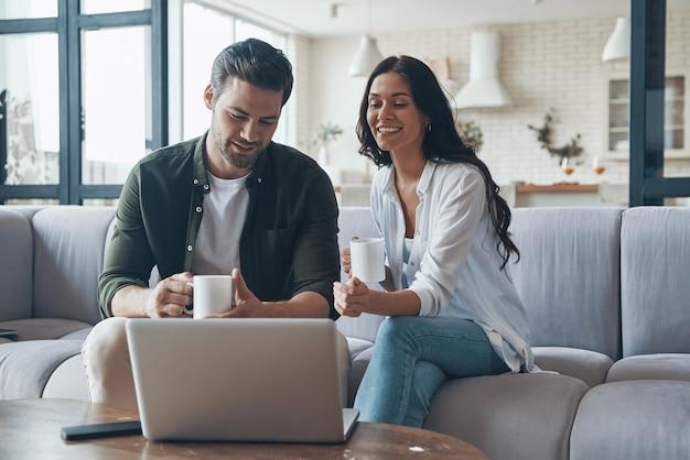 Красивая молодая пара пьет кофе и смотрит на ноутбук, сидя на диване у себя дома