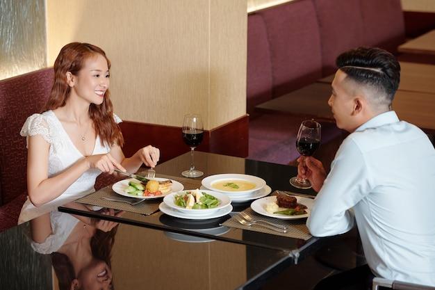 와인을 마시고 저녁을 먹고 멋진 레스토랑에서 이야기하는 아름다운 젊은 부부
