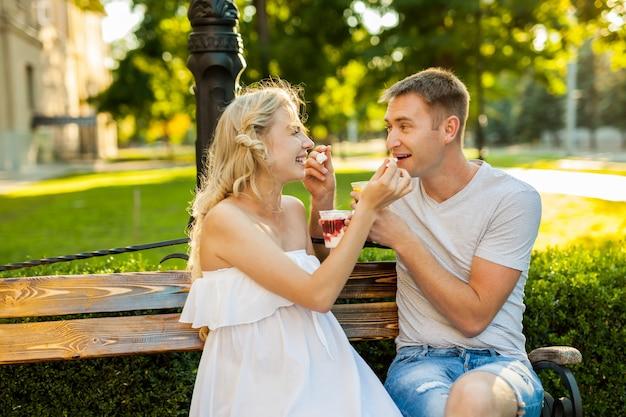 路上でアイスクリームを食べて美しい若いカップル