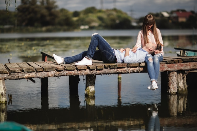 Beautiful young couple embracing and smiling while sitting on the pier