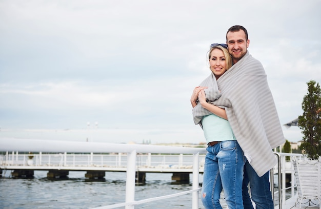Beautiful young couple embracing, standing on a pier near water.