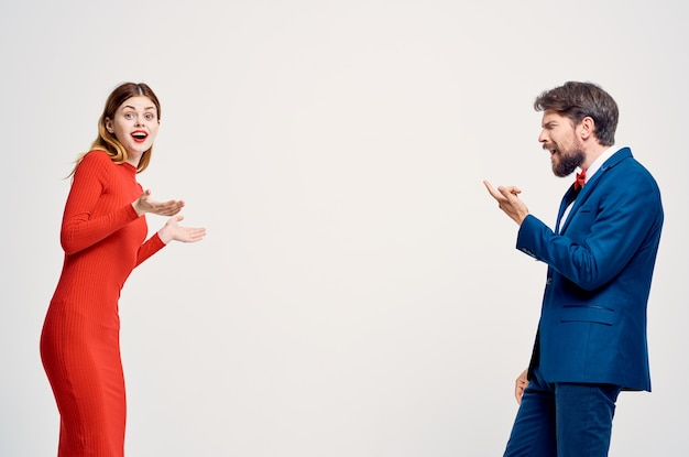 Beautiful young couple emotions hand gestures light background