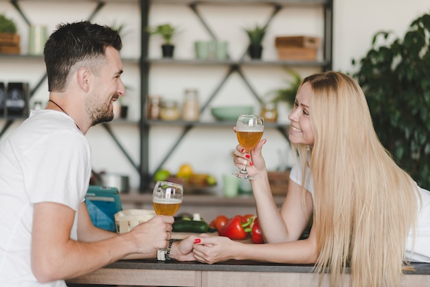 Beautiful young couple enjoying drinks holding beer glasses