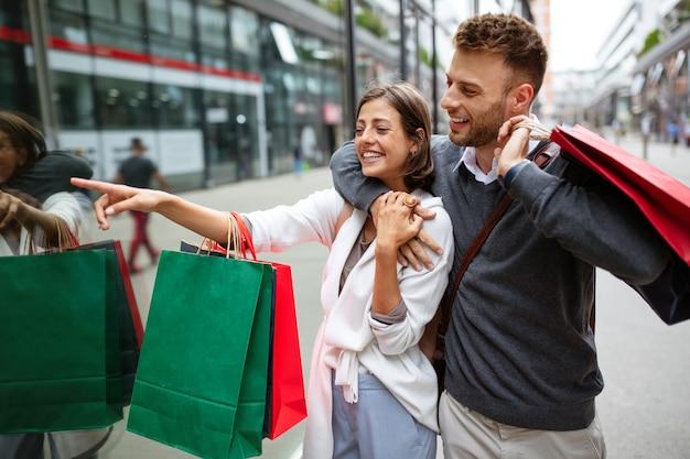 Красивая молодая пара, наслаждаясь покупками, весело вместе. потребительство, любовь, свидания, концепция образа жизни