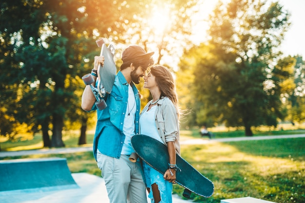 街のスケートボードパークで屋外で楽しんだり、キスしたり、抱き合ったりする美しい若いカップル。