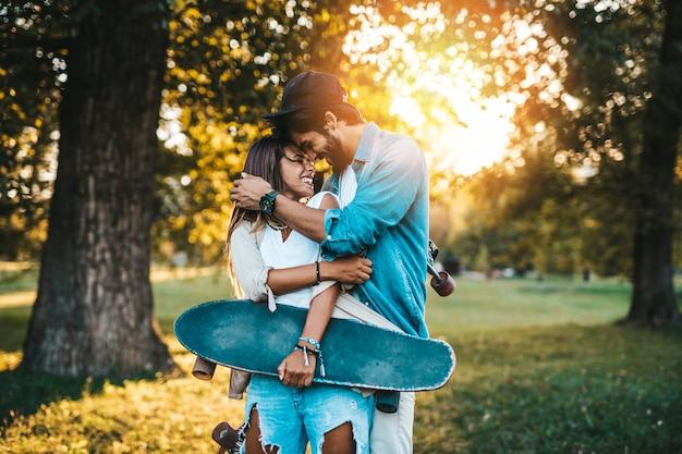 街のスケートボードパークで屋外で楽しんだり、キスしたり、抱き合ったりする美しい若いカップル