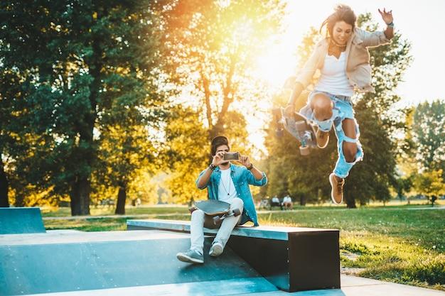 アウトドアを楽しんだり、街のスケートボードパークで写真を撮ったりする美しい若いカップル。