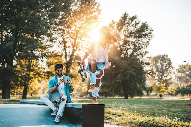 アウトドアを楽しんだり、街のスケートボードパークで写真を撮る美しい若いカップル
