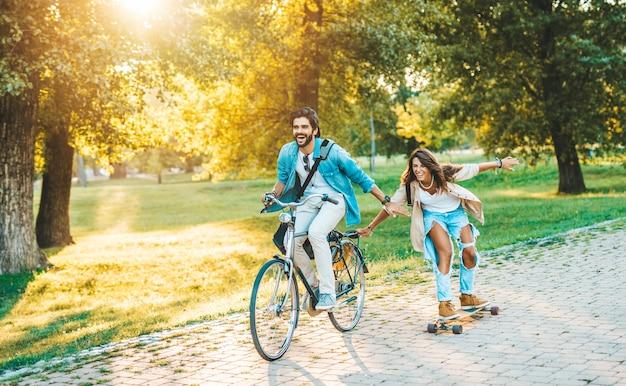 街のスケートボードパークでアウトドアを楽しんだり、自転車に乗ったりする美しい若いカップル。