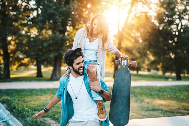街のスケートボードパークでアウトドアを楽しんでいる美しい若いカップル。