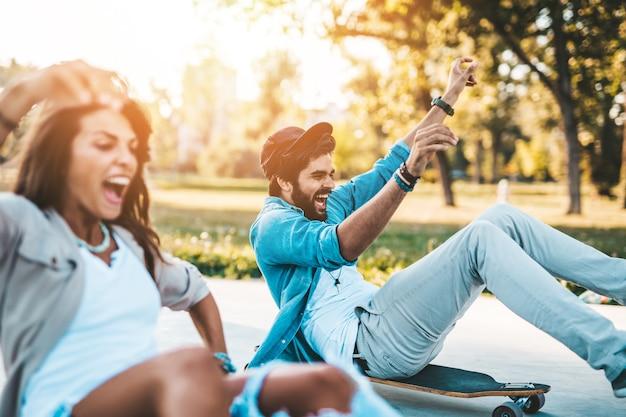 街のスケートボードパークでアウトドアを楽しむ美しい若いカップル