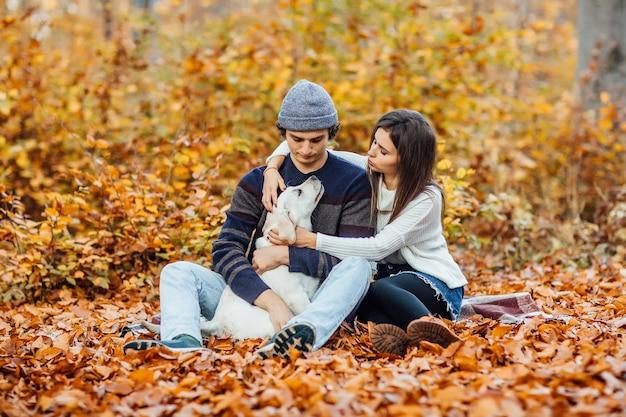 黄金のラブラドールと森でピクニックの時間を楽しんでいる美しい若いカップル。