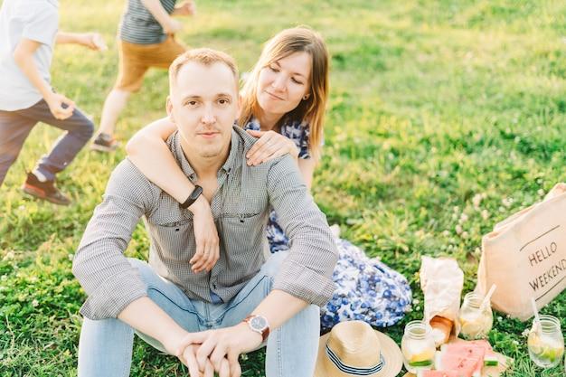 Красивая молодая пара, наслаждаясь пикником на закате, они сидят на лугу на траве и