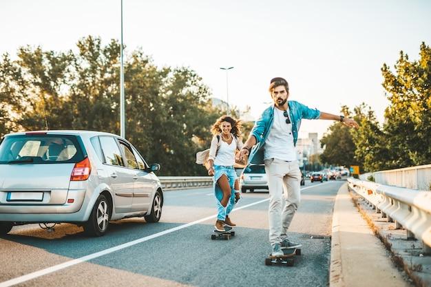 街の通りでスケートボードを楽しんでいる美しい若いカップル