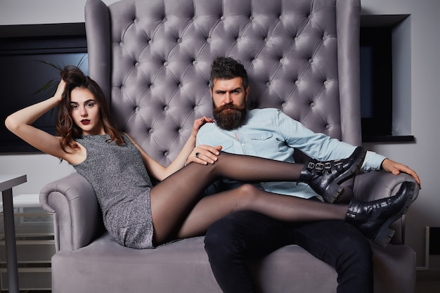 Beautiful young couple in formal wear looking at the camera while sitting in a couch together