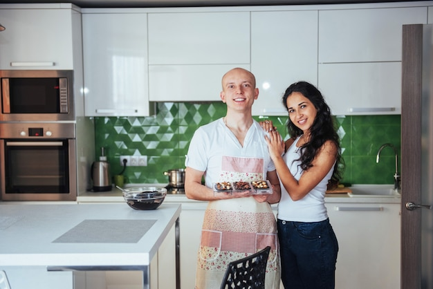 Beautiful young couple graphed miling at the camera while cooking in the kitchen at home.