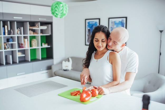 Beautiful young couple grinds vegetables together in the kitchen.