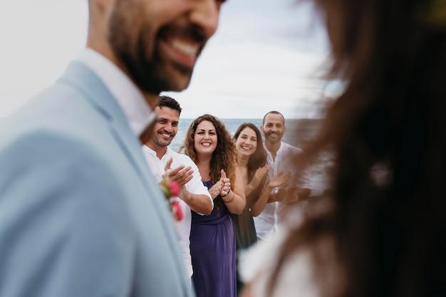 ビーチでの結婚式をしている美しい若いカップル