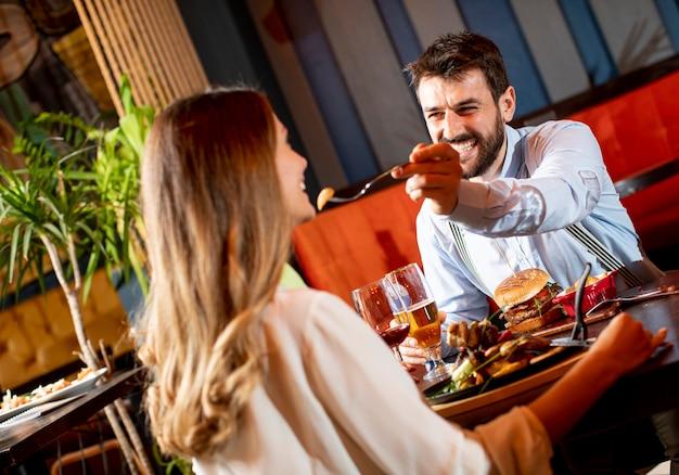 レストランで夕食を食べて美しい若いカップル