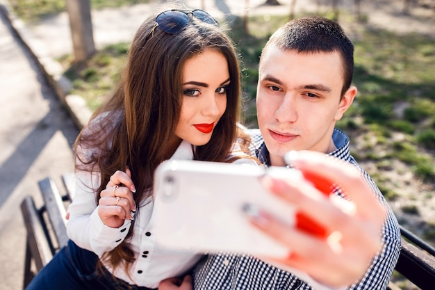 Beautiful young couple having fun on a bench in the park