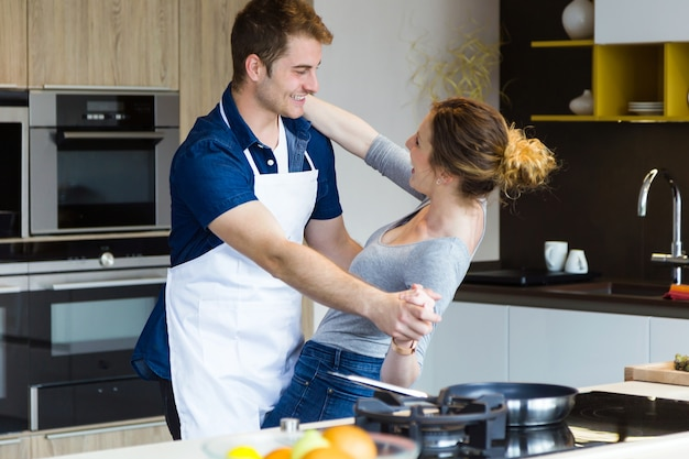 Beautiful young couple having fun in the kitchen at home.