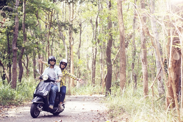 Beautiful young couple in helmets riding a scooter through forest