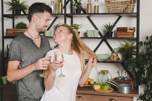 Beautiful young couple holding champagne flute in the kitchen