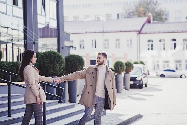 야외에서 걷는 동안 손을 잡고 웃 고 아름 다운 젊은 부부