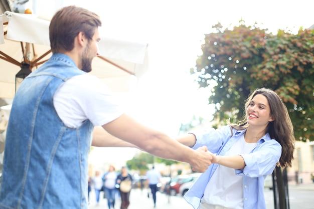 街の通りに立っている間手をつないで回転している美しい若いカップル。