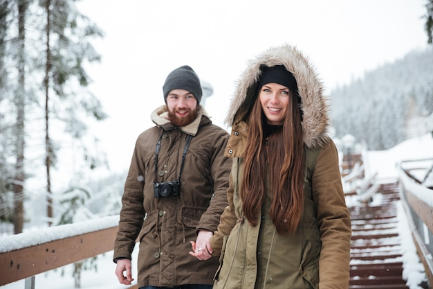 Beautiful young couple holding hands and walking down the stairs together in winter