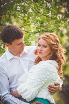 Красивая молодая пара обнимается на прогулке в весеннем яблоневом саду