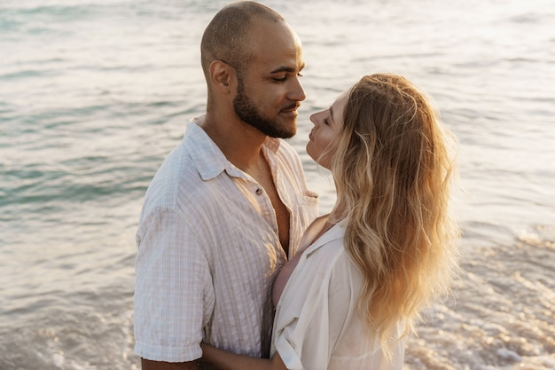 水辺のビーチで抱き締める美しい若いカップル